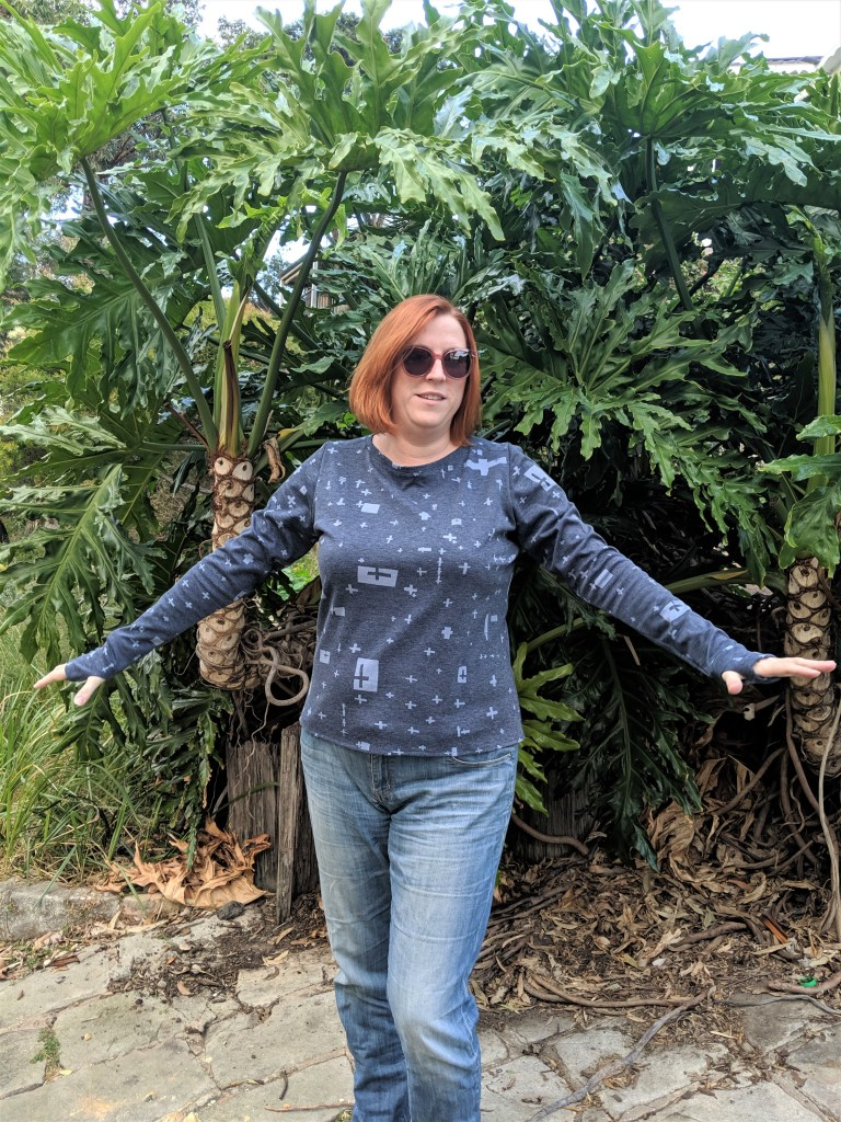 Author standing in front of plants wearing a blue long sleeved top with thumb cuffs.  Her arms are outstretched to show the thumb cuffs.  The top is blue with a random cross design,
