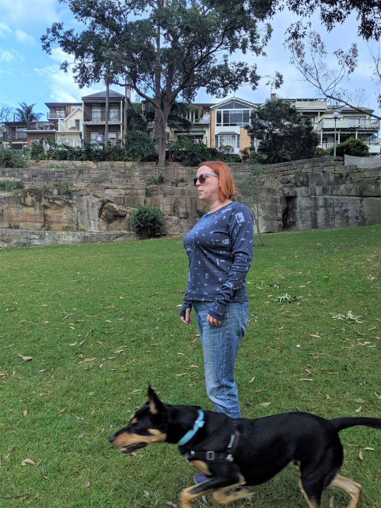 Author standing sideways on in blue long sleeved top in a part.  A very handsome Kelpie (her dog) is running past her.