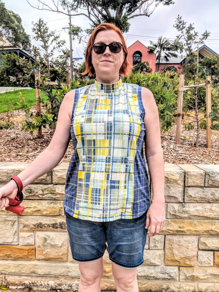 The author facing the camera wearing a yellow and blue plaid top and sunglasses