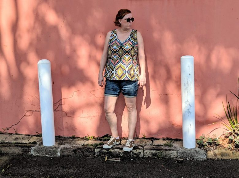 The author standing in front of a terracotta coloured wall wearing the v neck cashmerette top and denim shorts.