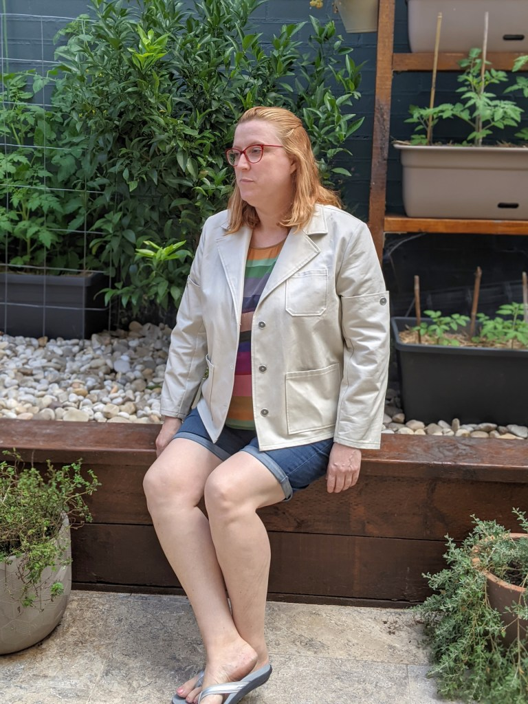 The author sitting on a wooden bench in the backyard wearing denim shorts, a rainbow top and the cream jacket.  The jacket is unbuttoned and she is looking away from the camera.