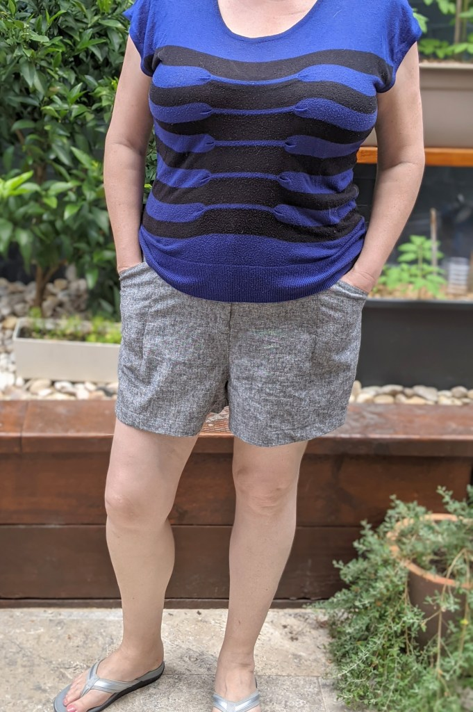 The author standing front to the camera.  She is wearing grey shorts and a blue and black striped top.. She has her hands in her pockets