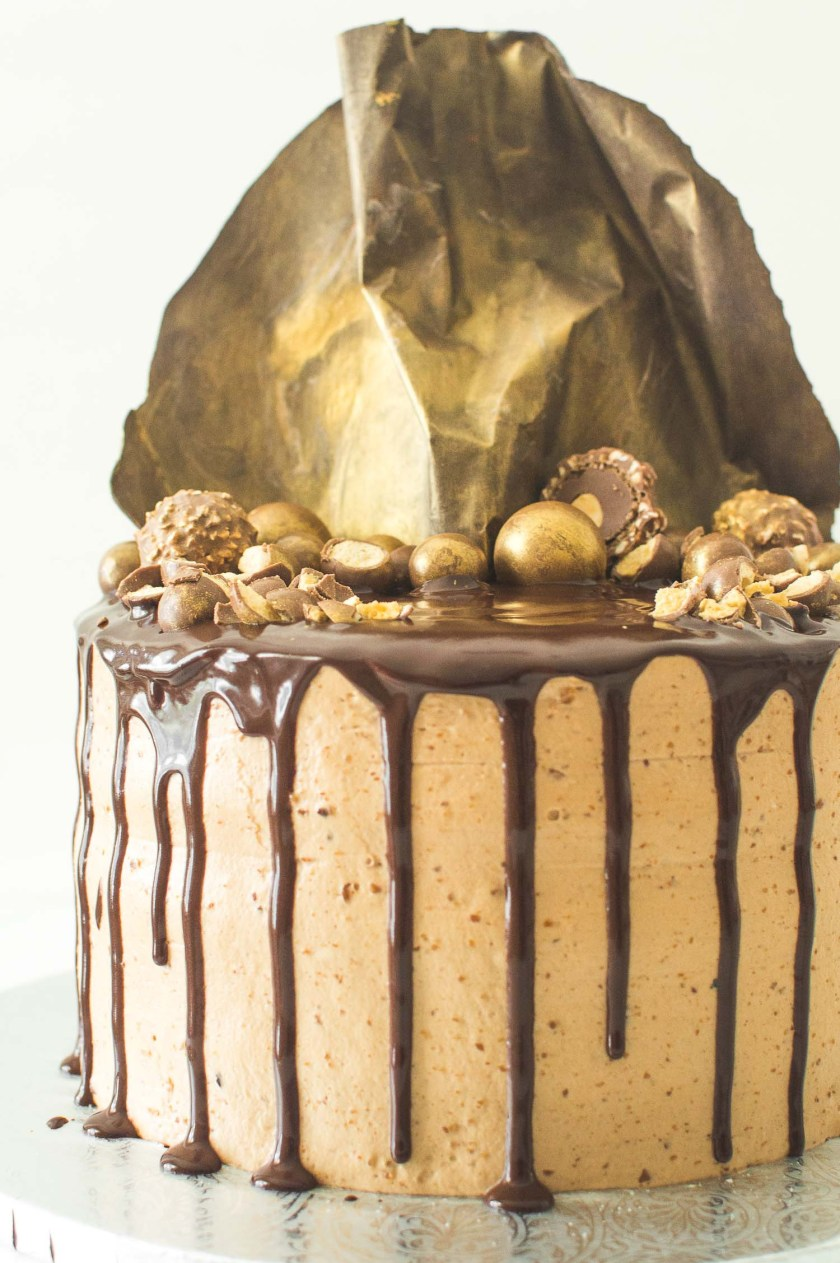 A tall, decadent gold hazelnut praline ganache cake topped with gold luster dust brushed onto Maltesers, Ferrero Rocher and a handmade chocolate sail.