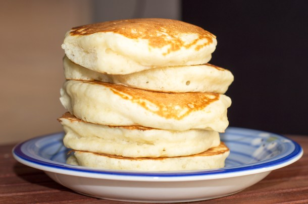 A delicious stack of five extra fluffy pancakes stacked atop a blue plate.