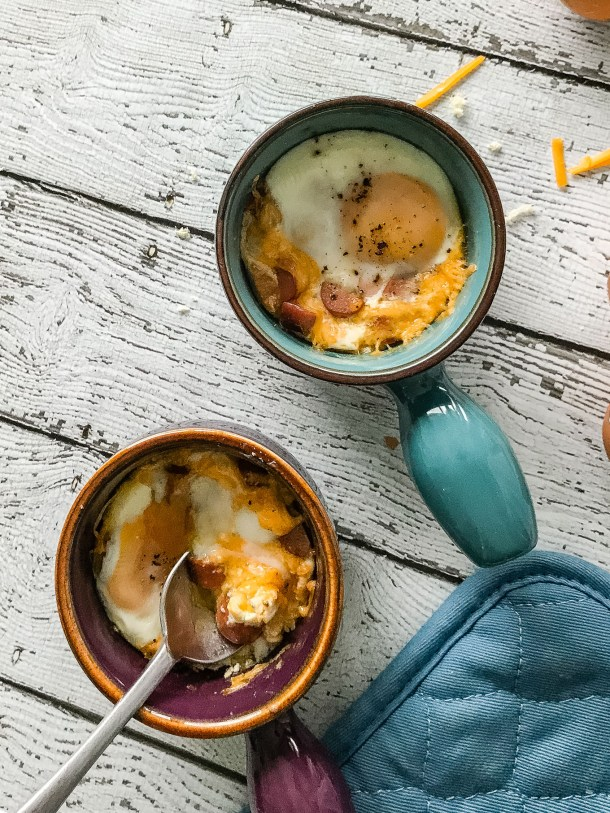 A vertical overhead shot of Cheesy Oeufs en Cocotte / Eggs in Pots, with a spoon cutting into one of the eggs.