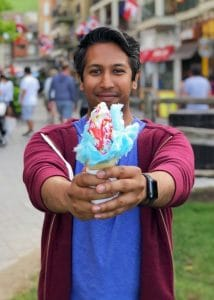 A photo of Riz wearing a maroon hoodie, holding forward a colourful ice cream cone.