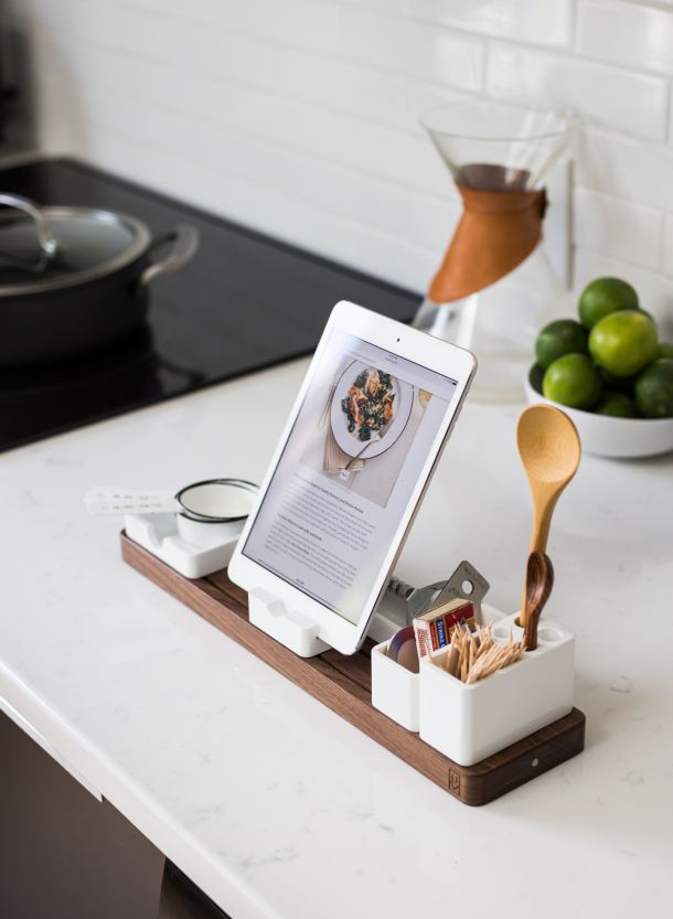 A 3/4 quarter view of an iPad with a recipe on it, on a stand that also include cooking utensils.