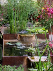 A naturally rusted steel water feature draws attention in this garden