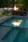 Rusted fire troughs illuminate the garden at night