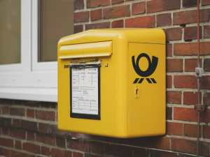 A yellow mailbox on a brick wall, as an example of who to notify when moving home.