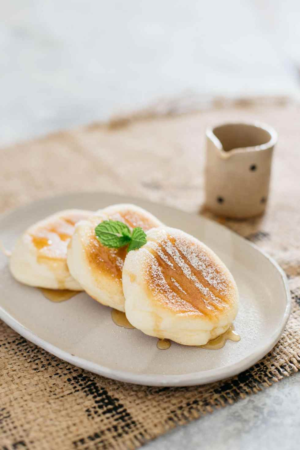 three souffle pancake served on an oval plate dusted with icing sugar and syrup
