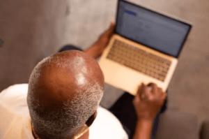 bald man using a laptop