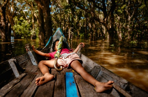 Sleeping girl on boat in flooded forest