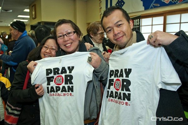 A group of people hold up 'Pray for Japan' T-shirts at a fundraiser to help the Canadian Red Cross aid disaster relief in Japan on Sunday, March 20, 2011. (TED GRANT / CHRISD.CA)