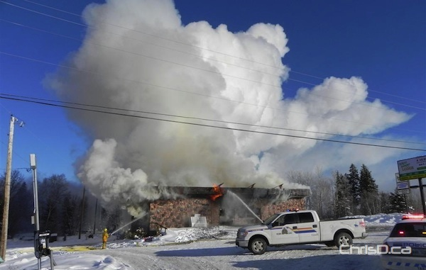 Firefighters work to contain a fire at the Bakers Narrow Lodge on Saturday, February 4, 2012. (RCMP HANDOUT)
