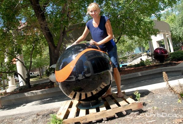 Artist Erica Swendrowski poses next to one of her giant glass marbles as part of a new downtown art exhibit titled, 'Marbles on Portage,' Friday, July 27, 2012. (STAN MILOSEVIC / CHRISD.CA)