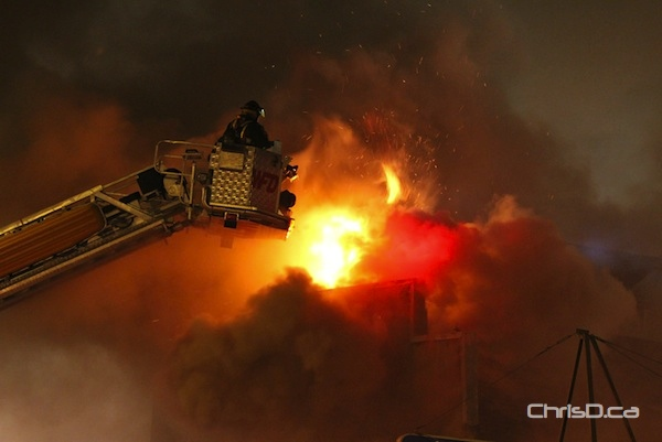 A firefighter uses an aerial ladder to get a handle on a massive fire in the 500 block of Notre Dame Avenue on Saturday, September 8, 2012. (HOWARD WONG / FOR CHRISD.CA)