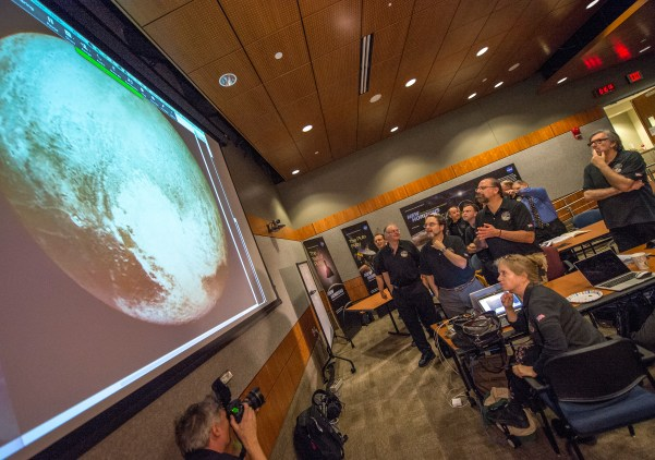 Members of the New Horizons science team react to seeing the spacecraft's last and sharpest image of Pluto before closest approach later in the day, Tuesday, July 14, 2015, at the Johns Hopkins University Applied Physics Laboratory (APL) in Laurel, Maryland. NASA's New Horizons spacecraft was on track to zoom within 7,800 miles (12,500 kilometers) of Pluto on Tuesday. (Bill Ingalls/NASA via AP)