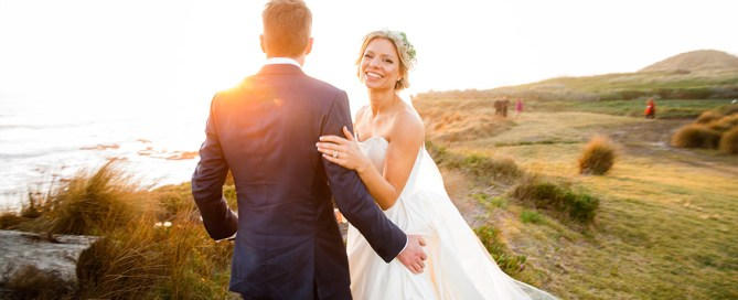 Melbourne Wedding Photographer photographing bride and groom on a cliff edge in Phillip Island with a beautiful sunset