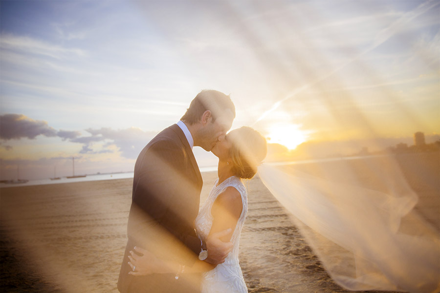 Melbourne Wedding Photographer taking photos of a bride and groom in front of an epic sunset in St Kilda