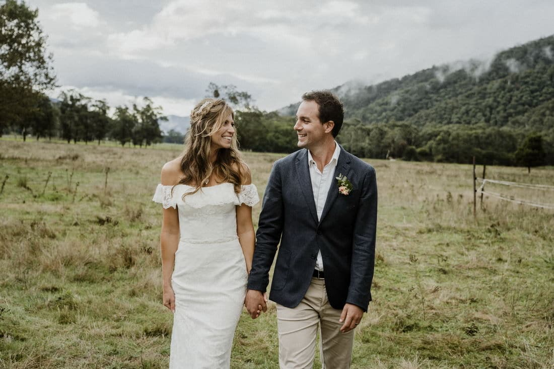 Bride and groom walking through the field at The House at Smoko by Bright Wedding Photographer