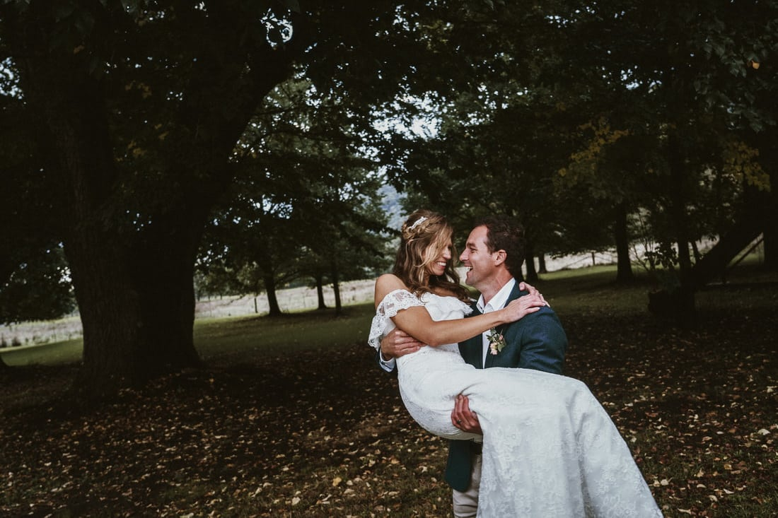 Gorgeous wedding photography of a groom carrying the bride at The House at Smoko by Mt Beauty wedding photographer
