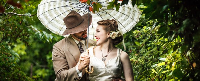 Melbourne Wedding Photographer with bride and groom holding umbrella in the rain in Macedon Ranges