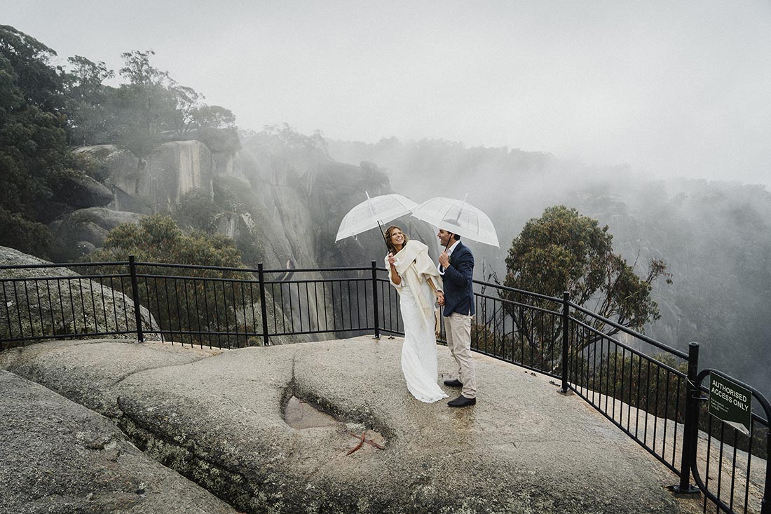 Mt Buffalo Wedding Photographer photographing a bride and groom with umbrella's overlooking the mountains