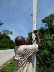 "Pastor Lesly attaches plaque ""Declaring God's Glory Over Haiti"""