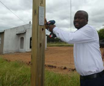 Pastor Godfrey attaching plaque
