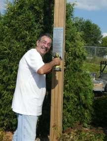 Pastor Bill Hieb attaching plaque