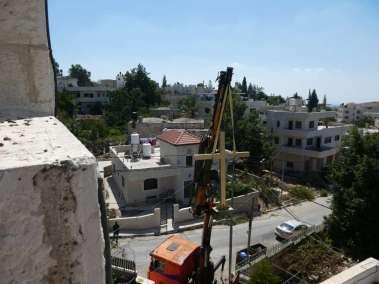 Crane lifts Cross toward the roof