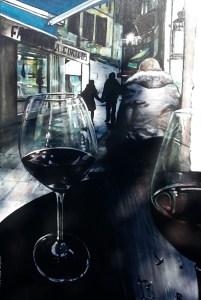 La nuit un homme assis de dos et en 1er plan un grand verre de vin rouge