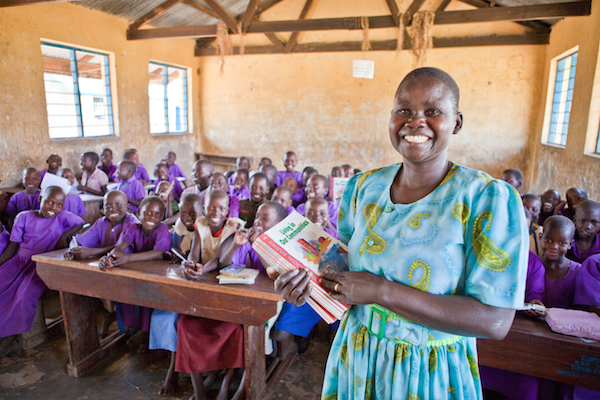 Aguiang Agnes, a teacher, holds textbooks donated by World Vision Canada to students at Tubur Primary School, Tubur, Uganda. Photo by Gary Dowd, World Vision Canada.