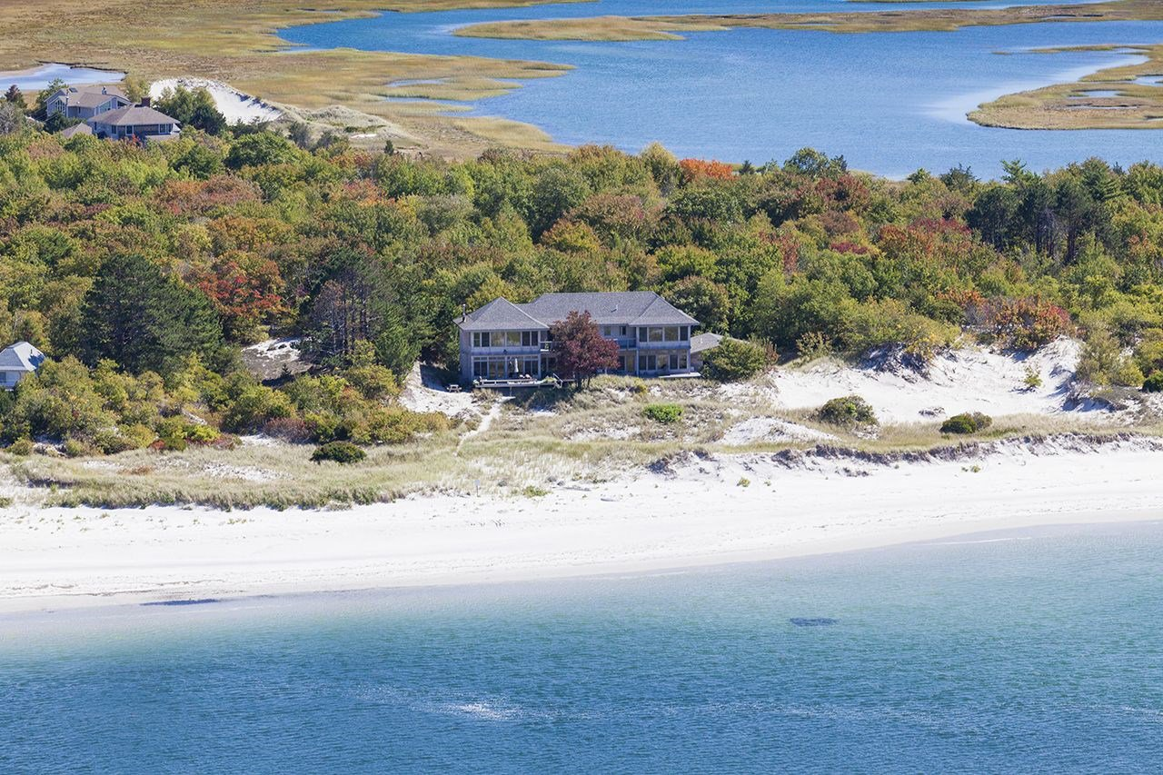 5 Bedrooms, 4,921 sq. ft. A rare opportunity to own a spectacular beachfront home located on Wingaersheek Beach in Gloucester, prized for its quiet privacy, unspoiled charm, and sweeping views over conservation land, this property features generous space for entertaining and outdoor oceanfront living including a potential mooring, as well as kayaking, swimming, and dramatic sunsets. Nestled in the dunes overlooking Crane Beach, the Essex River, and the Atlantic Ocean, this shingle-style contemporary built in 2007 is the ultimate in beachfront living with magnificent ocean-facing outdoor decks.