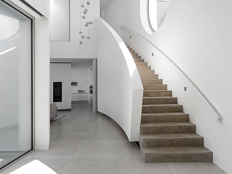 Outros destaques da Elliptical House na Luz, Portugal, incluem interiores minimalistas e uma escadaria de mármore que segue a curva do edifício.
