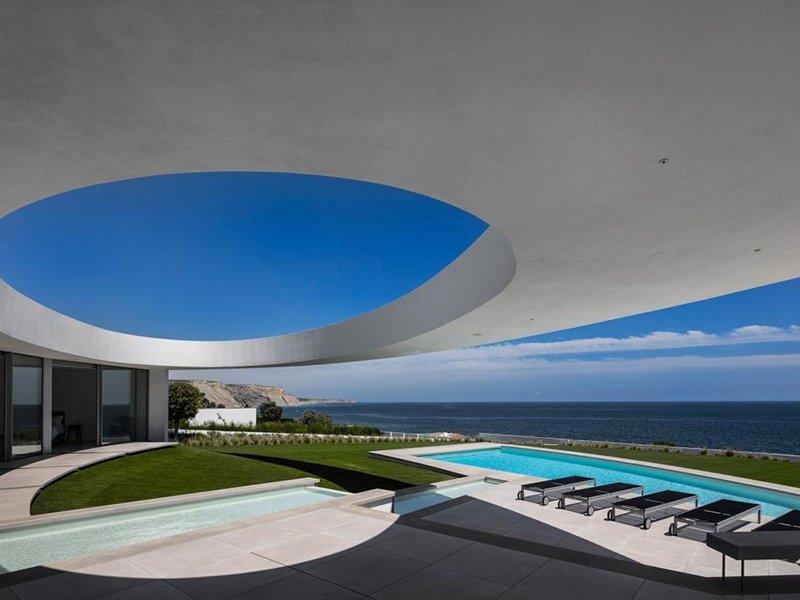 Um largo oval flutuante sutilmente determina os limites do pátio central da Casa Elíptica na Luz, Portugal.
