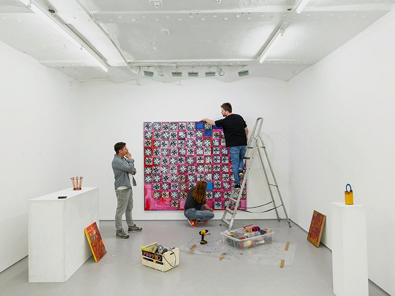 Kim Savage, director of London's FOLD gallery, looks on as contemporary artist Dominic Beattie checks his ink-and-spray-paint work <i data-recalc-dims=