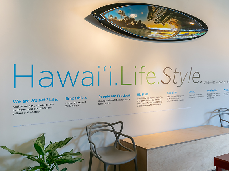 A surfboard and the ethos of Hawaii Life are displayed on the wall of the brokerage's offices