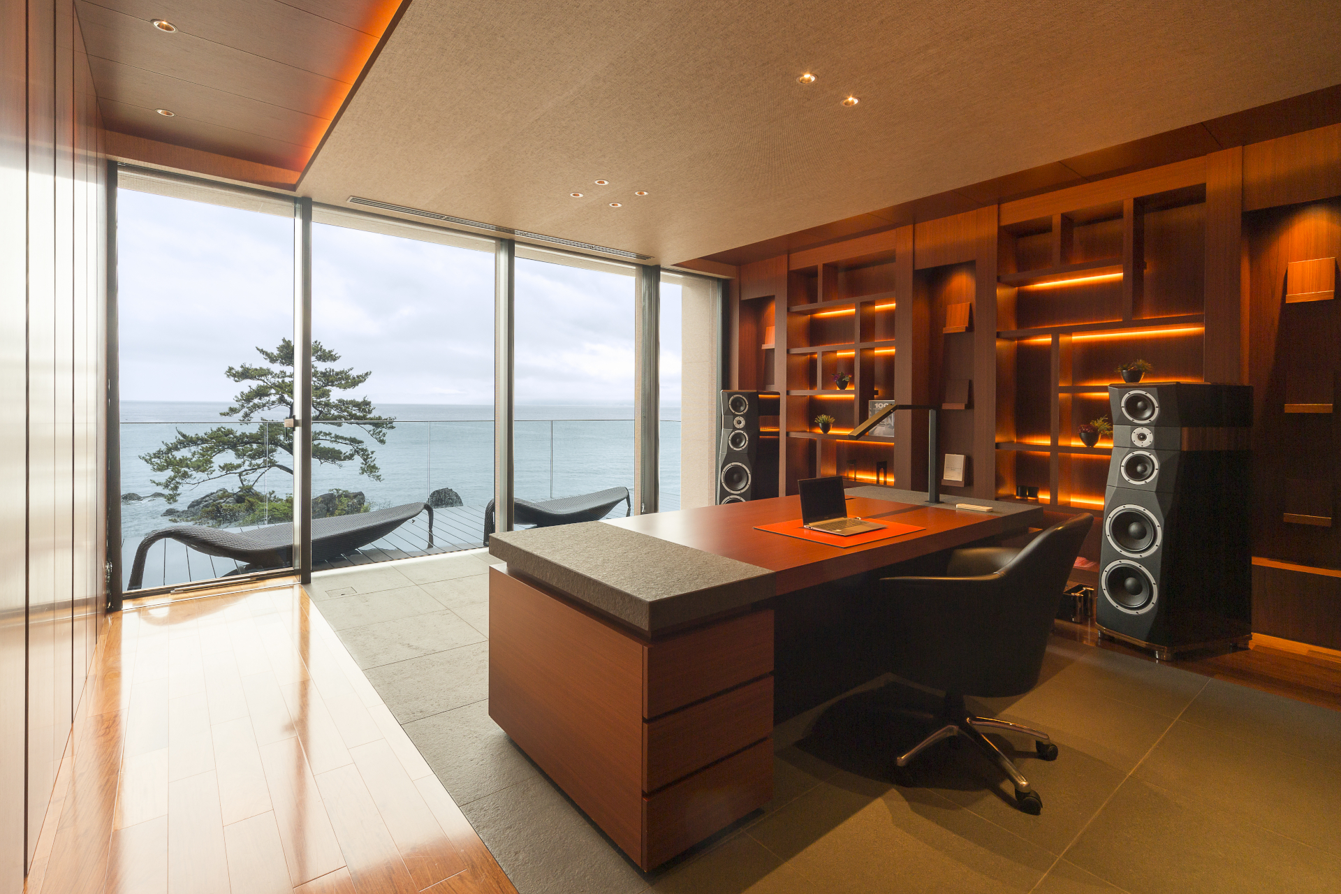 This contemporary estate in Ashigarashimo-Gun, Japan, has a contemporary office with recessed lighting, bookshelves, and surround-sound speakers. Sliding glass doors open to a deck facing Sagami Bay.