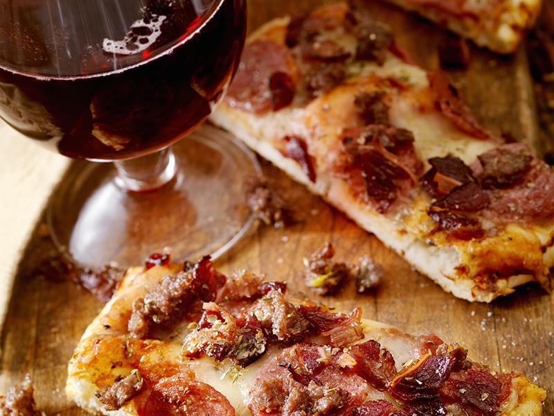 Pepperoni pizza slices with red wine