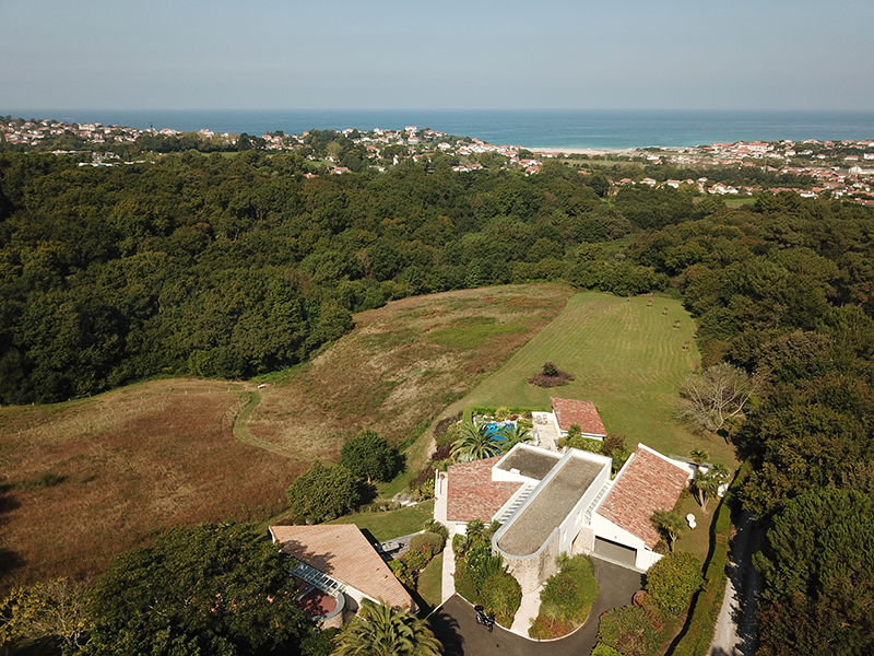 An aerial view of a villa with the sea in the background