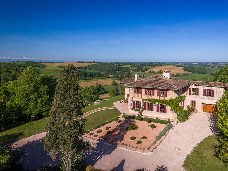 A magnificent farm house with rolling countryside and mountain views behind it