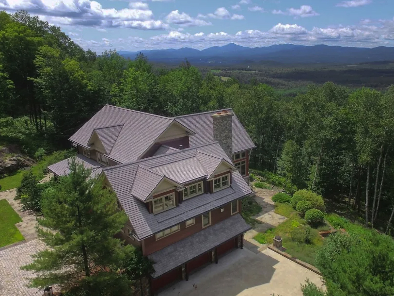 Aerial view of a large home and woodland