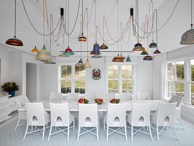 A white and blue dining room with many colorful ceiling lamps