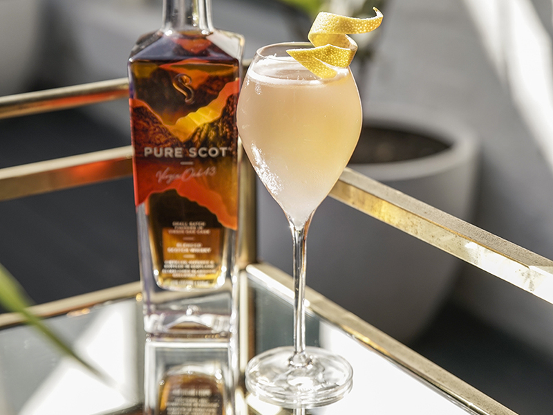 Cocktail in a champagne flute with bottle of whisky