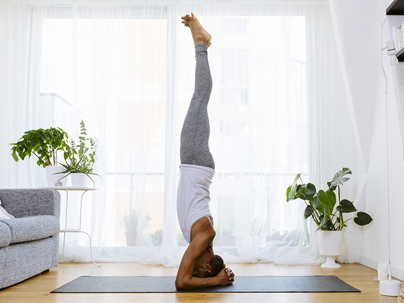 Woman practicing yoga dynamic headstand at home