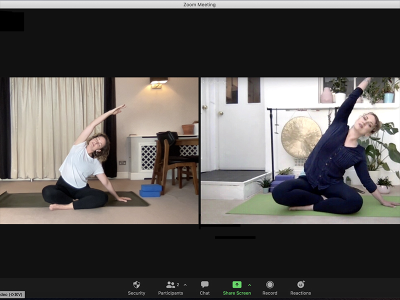 Two women practicing home yoga over a Zoom call