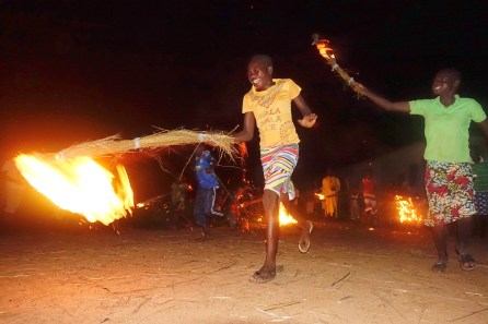 two girls holding bundles of grass that are on fire run towards the camera with big smiles on their faces. a fire is in the background under a dark night sky