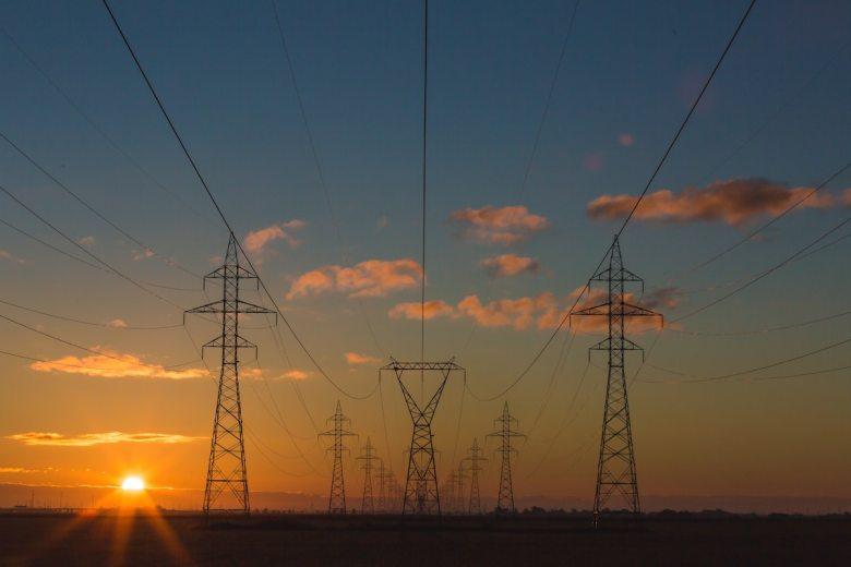 Energieverbrauch Internet: Strommasten und Hochspannungsleitungen in der Dämmerung
